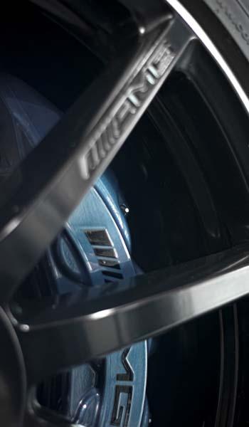 blue AMG brake caliper behind black wheel